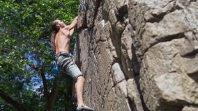 Young muscular man rock climber climbing on tough sport route, searching, reaching and gripping hold.