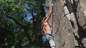 Young muscular man rockclimber climbing on tough sport route, searching, reaching and gripping hold.