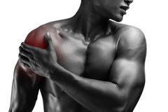 Young muscular man with shoulder pain , isolated on white backgr. Ound, monochrome photo Royalty Free Stock Photography
