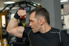 Young muscular man showing his biceps in gym.  Stock Photo