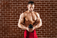 Young muscular man showing his perfect body and shaker stock photo