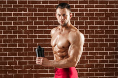Young muscular man showing his perfect body and shaker royalty free stock image