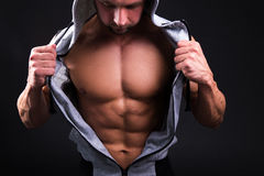 Young muscular man showing his torso over grey Royalty Free Stock Photography