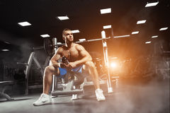 Young muscular man sitting with a bottle of water in the gym Royalty Free Stock Images