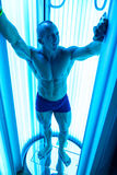 Young Muscular Man At Solarium In Beauty Salon Stock Photos