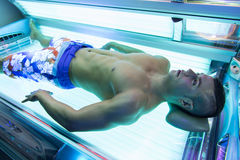 Young Muscular Man At Solarium In Beauty Salon Stock Image