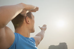 Young Muscular Man Stretching Toward the Sun Stock Photo