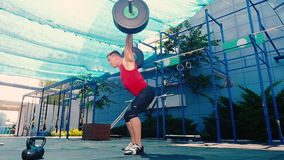 Young muscular man training with barbell on the street stock video