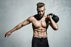 Young muscular man training with kettlebells. Photo of man with naked torso on grey background. Strength and motivation stock images