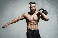 Young muscular man training with kettlebells. Photo of man with naked torso on grey background. Strength and motivation stock photo