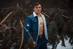 Young muscular man in unbuttoned jacket with bared breast stands next to pine tree in winter forest. Young muscular man in unbuttoned jacket with bared breast royalty free stock image