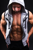 Young muscular man in vest with hood over grey. Background Stock Photos