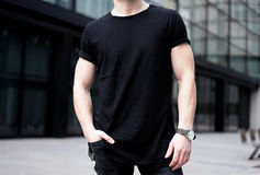 Young muscular man wearing black tshirt and jeans posing in center of modern city. Blurred background. Hotizontal mockup royalty free stock photo