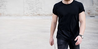 Young muscular man wearing black tshirt and jeans walking on the urban district. Blurred background. Hotizontal wide Stock Photo