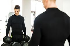 Young muscular man working out in a gym and lifting weights. With his reflection showing in a mirror royalty free stock images