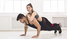 Young muscular man doing push ups with girl on back. Young muscular men doing push ups with girl on back in studio, panorama, copy space royalty free stock photos