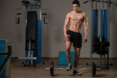 Young Muscular Men Standing By The Barbell Royalty Free Stock Images