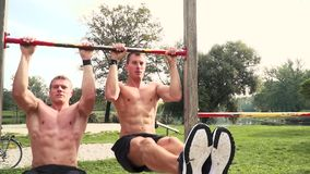 Men and women doing various bodyweight exercises at the horizontal bar. Young, muscular men and women doing various bodyweight exercises at the horizontal bar stock video footage