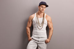 Young muscular rapper leaning on a wall. Young muscular rapper with a gold chain leaning against a gray wall and looking at the camera Stock Image