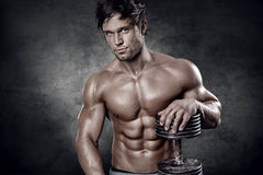 Young muscular sexy man standing in front of wall Royalty Free Stock Images