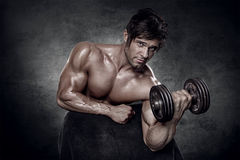 Young muscular sexy man workout in gym Stock Photos