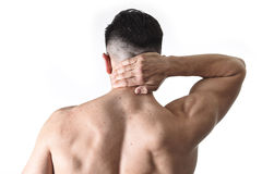 Young muscular sport man holding sore neck massaging cervical area suffering body pain. Back of young muscular sport man holding sore neck with his hand and Royalty Free Stock Images