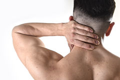 Young muscular sport man holding sore neck massaging cervical area suffering body pain. Back of young muscular sport man holding sore neck with his hand and Stock Images