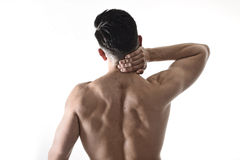Young muscular sport man holding sore neck massaging cervical area suffering body pain. Back of young muscular sport man holding sore neck with his hand and Stock Image