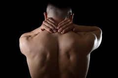 Young muscular sport man holding sore neck massaging cervical area suffering body pain Royalty Free Stock Images