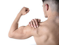 Young muscular sport man holding sore shoulder in pain touching massaging in workout stress. Young muscular sport man holding sore shoulder with hand touching or stock photo