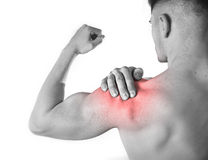 Young muscular sport man holding sore shoulder in pain touching massaging in workout stress Stock Photos