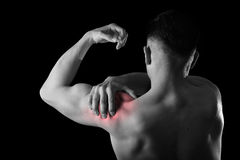 Young muscular sport man holding sore shoulder in pain touching massaging in workout stress. Young muscular sport man holding sore shoulder with hand touching or Royalty Free Stock Photo