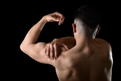 Young muscular sport man holding sore shoulder in pain touching massaging in workout stress. Young muscular sport man holding sore shoulder with hand touching or Royalty Free Stock Images