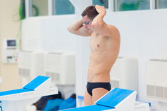 Young muscular swimmer preparing to start, puts his hat and glasses. Royalty Free Stock Photos
