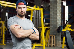Young muscular trainer standing arm with sarcastic look. Young muscular trainer standing arm cross looking in camera with sarcastic facial expression. Fitness royalty free stock photography