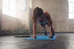 Young muscular woman doing core exercise. On fitness mat in the gym. Fit female doing press-ups during the training in the health club Stock Photography