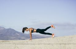 Muscular woman doing core exercise outdoors. Young muscular woman doing core exercise outdoors. Fit female doing press-ups during training session. Side view stock photography
