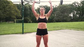 Young muscular woman is doing exercises with the barbell. Outdoor in the morning stock video