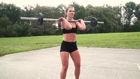 Young muscular woman is doing exercises with the barbell. Outdoor in the morning stock video footage
