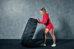 Young muscular woman flipping a tire on hard training with personal trainer at the garage gym. stock images
