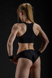 Young muscular woman posing on black Stock Photo
