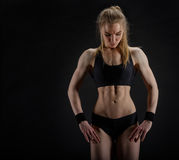 Young muscular woman posing on black Royalty Free Stock Images