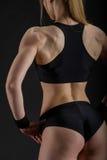 Young muscular woman posing on black Stock Photos