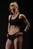 Young muscular woman posing on black Stock Image