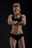 Young muscular woman posing on black Stock Images