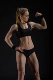 Young muscular woman posing on black Royalty Free Stock Photo