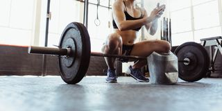 Weightlifter preparing for training with barbells at gym. Young muscular women clapping hands with chalk powder, preparing for barbell training in gym. Young royalty free stock photography