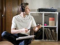 Young music lover man in casual and sitting at home in headphones with vinyl records stock photography