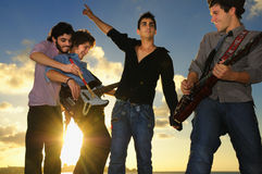 Young musical band with instruments at sunset royalty free stock images