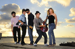 Young musical band posing  with instruments. Portrait of young musical band with 4 boys and a girl posing outdoors at sunset with instruments Stock Image